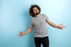 A curly-headed handsome man wearing a gray T-shirt is standing with a cheerful smile with his hands spread open and royalty free stock images