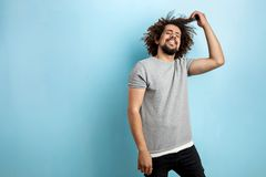 A curly-headed handsome man wearing a gray T-shirt is standing with a happy smile and touching his hair over the blue royalty free stock images