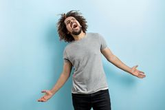 A curly-headed handsome man wearing a gray T-shirt is standing and laughing hard with his hands widly spread, looking. Upwards over the blue background stock photos