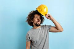 A curly-headed handsome man wearing a gray T-shirt is standing with a safety helmet and looking sideways over the blue stock photo