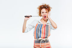Curly housewife in striped apron holding and playing with knife Stock Photo