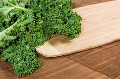 Curly kale leaves on cutting board Royalty Free Stock Image