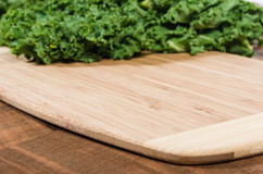 Curly kale leaves on cutting board Stock Images