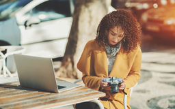 Curly lady with laptop and retro camera in street cafe Royalty Free Stock Photos