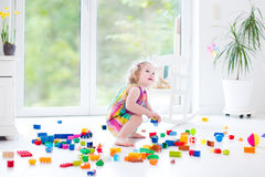 Curly laughing toddler girl playing with colorful blocks Royalty Free Stock Photos