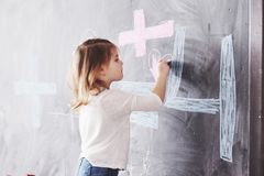 Curly little baby girl drawing with crayon color on the wall. Works of child. Cute pupil writing on chalkboard stock photography