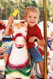 Curly little boy riding a carousel Royalty Free Stock Images