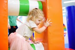 Curly toddler girl having fun in indoor leisure center for kids. Stock Photos