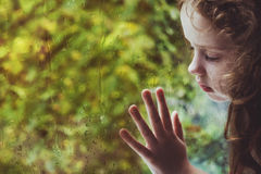 Free Curly Little Girl Looking Out The Rain Drop Window Stock Photography - 97036602