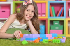 Curly little girl playing. With colorful plastic blocks Royalty Free Stock Images