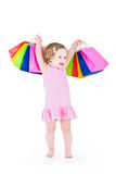 Curly little girl after sale with her colorful bags Royalty Free Stock Photos