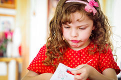 Curly little girl with scissors Royalty Free Stock Photos
