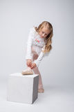 Curly little girl tying pointe, on gray backdrop Stock Photo