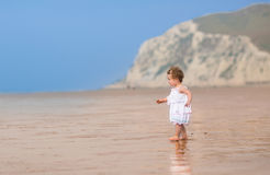 Curly little girl in a white dress on exotic beach Stock Photos