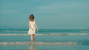 Curly little girl in white dress walking on the beach at sunset. Slow Motion. Happy Childhood, Freedom and Travel. Concept stock footage