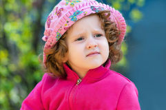 Curly little lady in the pink hat Royalty Free Stock Photo