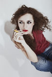 Curly long-haired brunette woman with yellow cigarette Stock Photos
