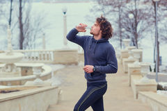 Curly Male runner drinks water from a bottle in park on the stai. Rs Stock Photography