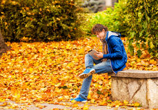 Curly man in blue jacket and scarf with computer tablet in autum Stock Image