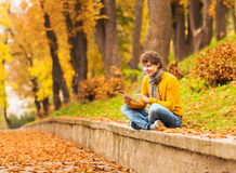 Curly man with computer tablet in autumn park Royalty Free Stock Images