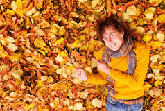 Curly man in sweater and scarf shows something on leaves backgrond Stock Image