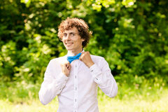 Curly man in white shirt and blue bow tie smiling Stock Photo