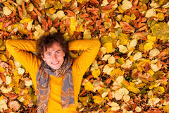 Curly man in yellow sweater and scarf lie on autumn leaves Stock Photo