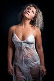 Curly mature  woman wearing lingerie posing black Royalty Free Stock Image