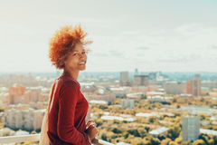 Curly mixed girl on balcony with cityscape behind stock image
