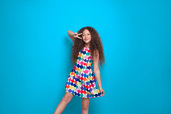 Curly model showing peace sign. Young curly woman in colorful dress posing cheerfully and showing two fingers on blue background Stock Image