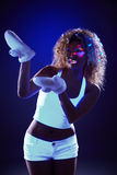 Curly model in warm gloves under UV light Royalty Free Stock Photography