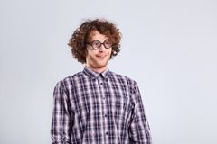 Curly nerd man in glasses with a stupid kind of funny emotion. Royalty Free Stock Photography