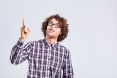Curly nerd man in glasses with a stupid kind of funny emotion. Royalty Free Stock Image