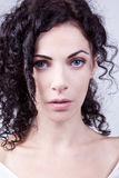 Curly noble blue-eyed woman Stock Images