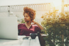 Curly pensive mixed lady with laptop in cafe outdoors Royalty Free Stock Images
