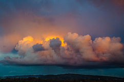 Curly pink cloud hangs over green mountain Royalty Free Stock Images