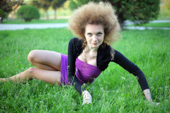 Curly, red-haired girl in the unusual position. Curly, red-haired girl in an unusual position in the park Stock Photo
