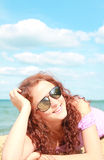 Curly redhead girl lying on the beach Royalty Free Stock Photo