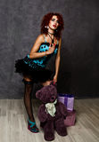 Curly redhead sexy girl looks like a doll for adult men. popsy posing with teddy bear and gift box Royalty Free Stock Photos
