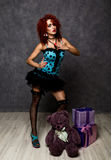 Curly redhead sexy girl looks like a doll for adult men. popsy posing with teddy bear and gift box Stock Photos