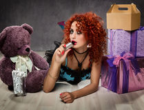 Curly redhead sexy girl looks like a doll for adult men. popsy sucks from a small bottle Royalty Free Stock Image