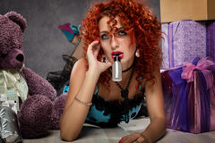 Curly redhead sexy girl looks like a doll for adult men. popsy sucks from a small bottle Stock Photos