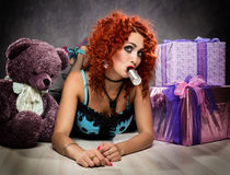 Curly redhead sexy girl looks like a doll for adult men. popsy sucks from a small bottle Royalty Free Stock Photos