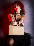 Curly redhead sexy girl looks like a doll holds a cardboard box or lunch box on a gray background. poppet for adult men. Royalty Free Stock Photography