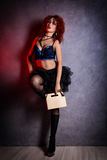 Curly redhead sexy girl looks like a doll holds a cardboard box or lunch box on a gray background. poppet for adult men. Royalty Free Stock Photos