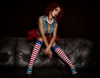 Curly redhead sexy girl sits on a leather sofa. Girl looks like a doll for adult men. Fashion style Stock Image