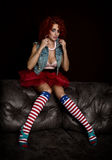 Curly redhead sexy girl sits on a leather sofa. Girl looks like a doll for adult men. Fashion style Royalty Free Stock Image