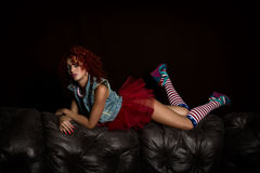 Curly redhead sexy girl sits on a leather sofa. Girl looks like a doll for adult men. Fashion style Stock Photography