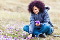 Curly redhead woman picking crocus flowers Royalty Free Stock Photo