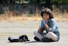 A curly schoolboy with a book Stock Image